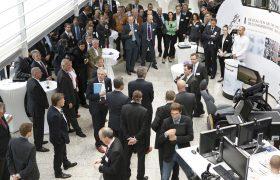 Rede in Eventhalle mit Aussteller und Besucher