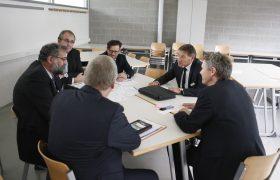 Teilnehmer sitzen zusammen und diskutieren