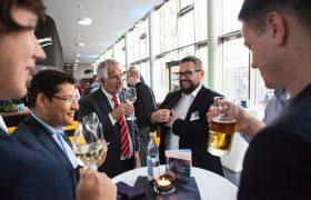 Besucher und Thomas Bauer unterhalten sich bei Getränken im Café